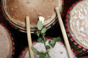 Photograph of URUBU drum skins with sticks and white flower
